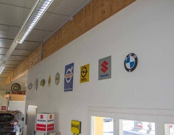 Wand im Innenraum mit Fahrzeugmarken-Blechschilder; unsere Trophäenwand