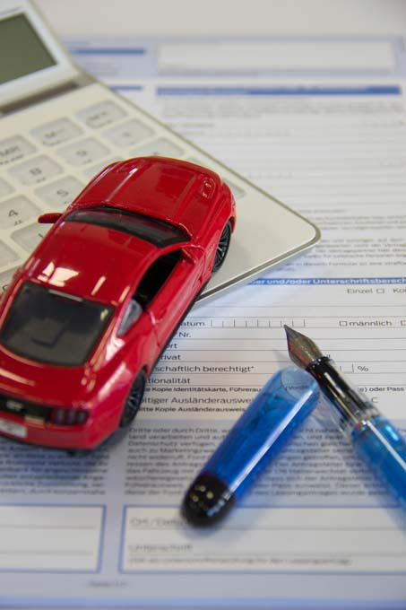 Modellauto steht auf Taschenrechner neben Leasingantrag und Füllfederhalter
