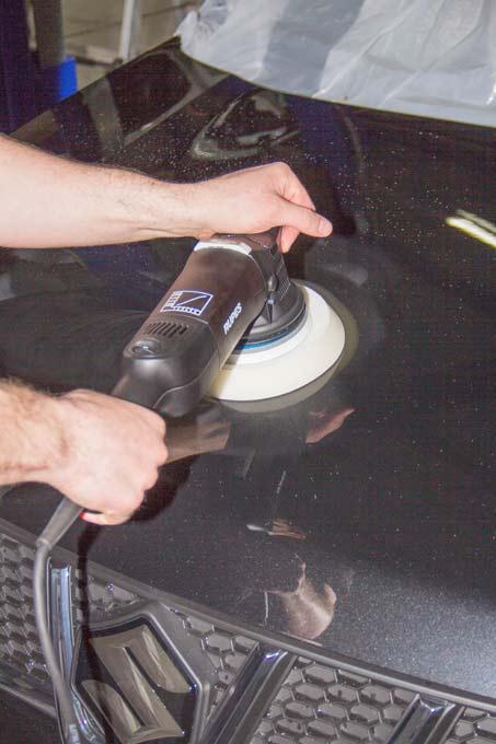 Ein Mitarbeiter poliert eine Motorhaube mit einer Exzenterpoliermaschine