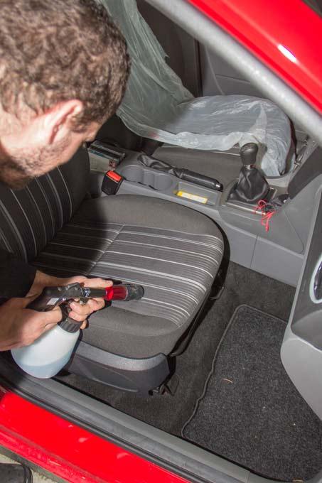 Ein Mitarbeiter entfernt mit einem Sprühgerät üble Gerüche auf einem Fahrzueugsitz