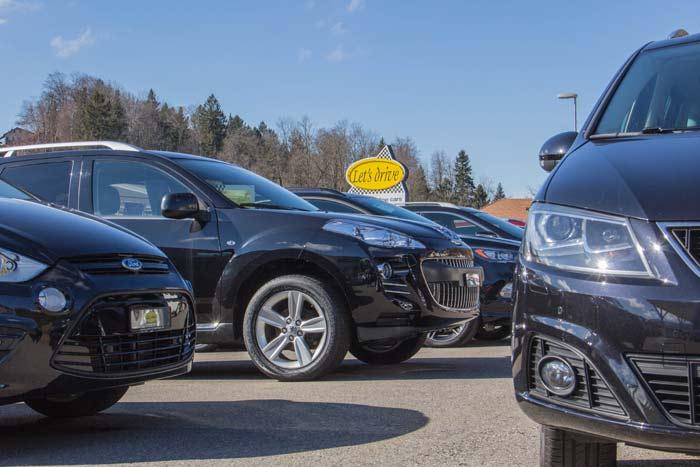 Sicht auf eine Reihe Occasionsfahrzeuge mit Firmentafel im Hintergrund; Gepflegte Occasionen