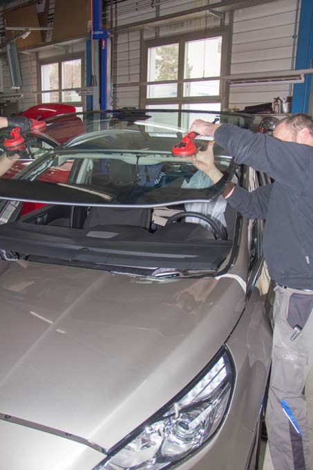 Eine neue Frontscheibe wird von zwei Mechaniker auf die Carrosserie aufgeklebt