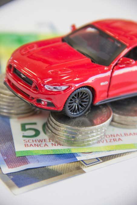 Modellauto steht auf Münzrolle und Noten