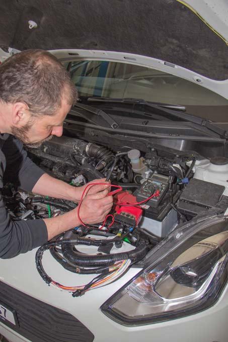 Ein Mitarbeiter sucht einen Fehler in der Motorelektronik und misst deshalb den Kabelstrang durch